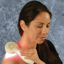 Woman treating shoulder for pain with dpl Nuve pain handheld